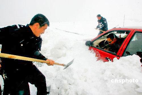 5月22日,受强冷空气的影响,新疆303省道哈密天山段遭遇大暴雪,积雪达50厘米以上,许多车辆和旅客被困雪中,新疆哈密市公安局交警大队的民警们闻讯后纷纷上路,营救被困群众和车辆。中新社发 朱正华 摄