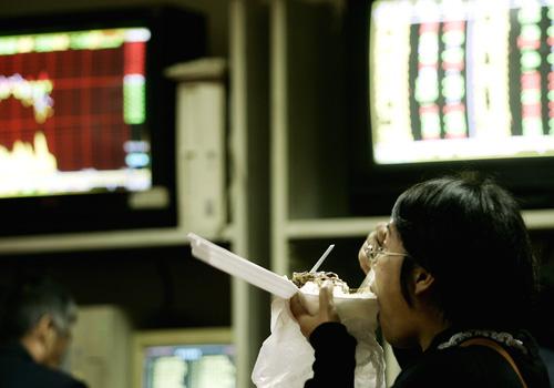 一位股民连吃盒饭的时候也紧盯显示屏。