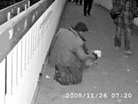 一老年乞讨者蹲在过街天桥上要钱。