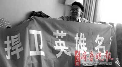 吕小山展示征集到400多个签名的条幅。