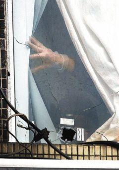 吴善九枪击案震惊社会,警方封锁现场搜证,对着窗户弹孔采证。