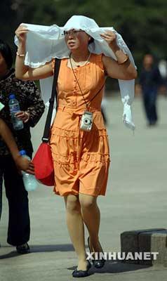 5月26日,一名在天安门广场游玩的游客用衣服遮挡阳光。