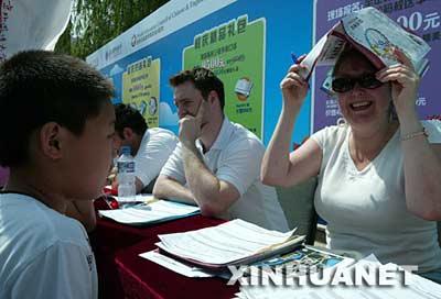 """5月26日,在""""北京市民外语活动周""""活动现场,一名外语教员头顶炎热的太阳用英语与一名北京小学生交谈。"""