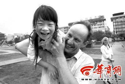 7岁的李晨与英国爸爸嬉戏玩耍,她的妈妈远远地看着父女俩 本报记者张宏伟摄