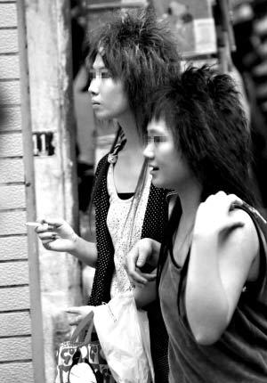 在广州上下九步行街,一名与朋友结伴而行的女孩边走边吸烟。