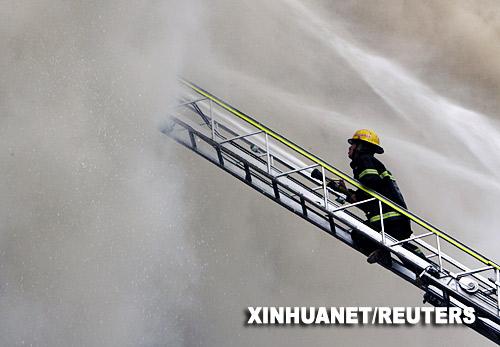 5月29日,在菲律宾首都马尼拉,一名消防队员攀上云梯灭火。
