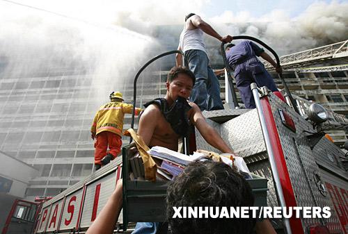 5月29日,在菲律宾首都马尼拉,消防队员搬运从发生火灾的大楼内抢救出的文件。