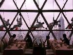 """坐在球体内用餐的游客和窗外清洗的""""蜘蛛人""""。"""