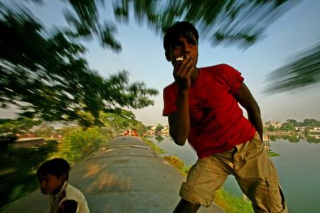 """""""没问题,看我在行进的火车顶上给你摆个抽烟的姿势"""",18岁的Helaluddin说。Helaluddin从他工作的塑料厂下班后经常以这样的方式回家。"""