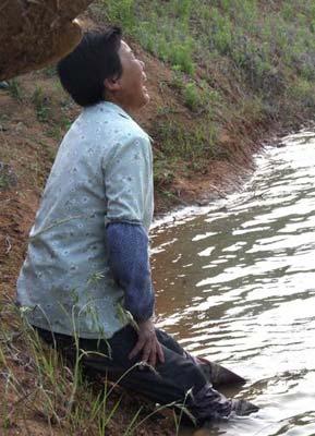 失去孩子的亲人只能无助的坐在水库旁边。图片来源:CFP