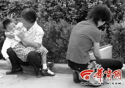 法庭外,张涛涛被奶奶抱着喂奶,妈妈则在一旁整理资料 记者宁峰/摄