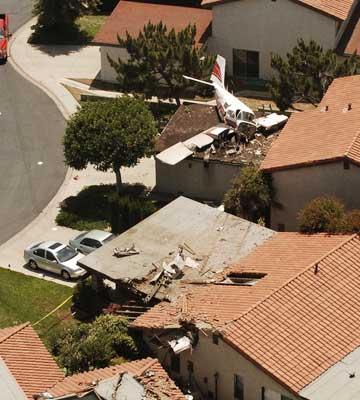 航拍小型飞机因失重迫降在车库房顶。