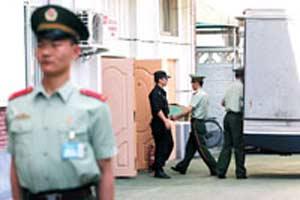 昨天,两辆警车押送着高考试卷抵达西城区考试中心。图为试卷被送进保密室。