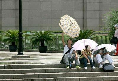 昨天,在人民广场一位学生举起雨伞仰望放晴的天空。昨天上海由雨转晴,天气经历了多种变化。早报记者张栋图