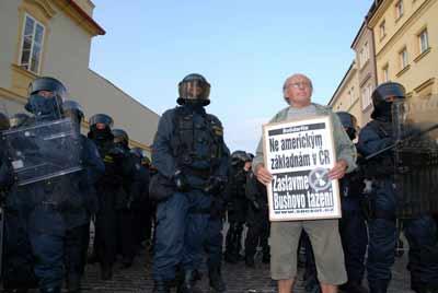 在6月4日布拉格城堡附近的示威中,一名愤怒的示威者冲入警戒线。他展示的标语牌上写着:不要在捷克建立美国基地,阻止布什扩张。(黄频 摄)