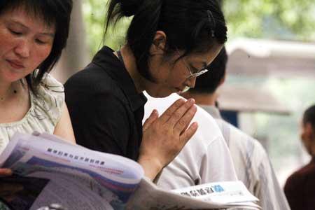一位母亲正在为孩子虔诚祈祷。记者许南平摄