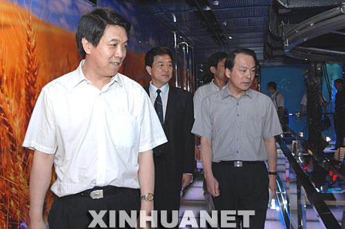 8日,中国气象局局长郑国光(左一)在新华社副社长何平陪同下参观新华社新闻大厦。
