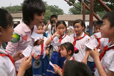 """图文:""""奥运志愿心乐团""""启动 许飞教学生唱歌"""