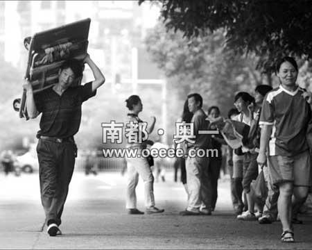 昨天上午,天河中学考场门口,因怕拉板车发出噪声影响学生考试,工人将板车抬在肩膀上走过学校。