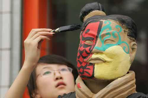 """2007年6月10日,西安市太华路金鑫涂料城门口,两名就读艺术系的大学生为自己创作的行为艺术作品""""秦兵马俑""""穿彩服。"""