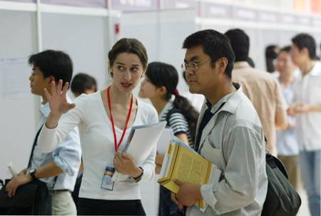 """5月27日,海外留学人才专场招聘会在北京市毕业生就业服务中心举行,一名""""海归""""正在与招聘方交谈。"""