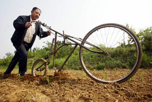 村民王福合日前用亲手改装的自行车耕起了承包的山坡玉米地。