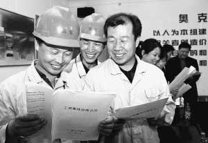 奥克集团的职工在阅读自己的工资集体协商合同。庄奉明摄