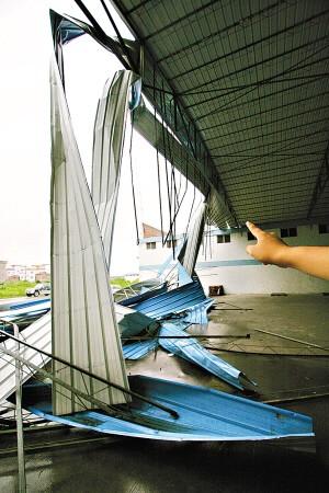 仓库顶的钢筋摇摇欲坠地悬挂着。