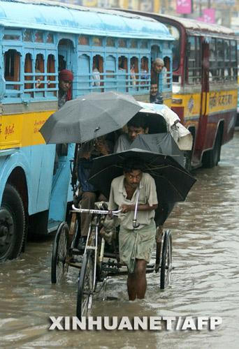 6月13日,在印度东部城市加尔各答,三轮车驾驶员推着乘客在被洪水淹没的街道上行走。