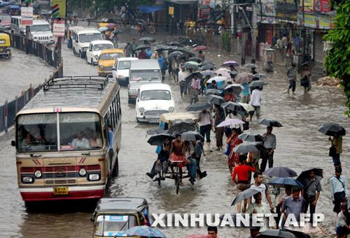 6月13日,在印度东部城市加尔各答,人们在被洪水淹没的街道上行走。