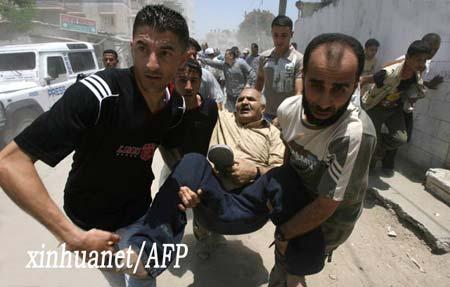 两名巴勒斯坦人帮助受伤者逃离现场。新华社/法新