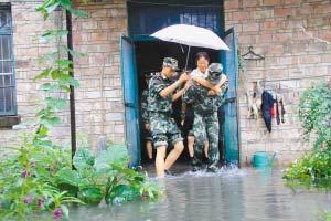 武警宜春市支队官兵在宜春市学府路二六七号将被水围困的老人从危房中背出来。