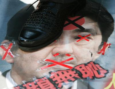 示威者脚踩被丑化的日本首相安倍晋三的画像。