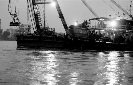 一艘悬挂着直径约1.5米的磁铁的打捞船,停靠在断桥下游约500米处。此区域先后停留4艘大型打捞船,并派出数艘小船来回作业。