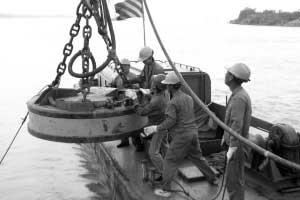昨日中午,磁铁船将磁铁块放入水开始吸附沉车残骸。 广州日报记者 龙成通 摄