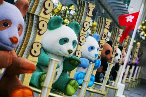 """2007年6月14日,人们从香港海港城外五光十色的""""熊猫""""旁走过。"""