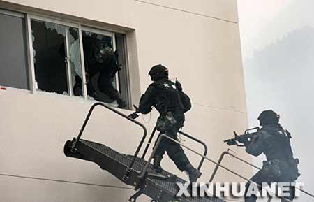 """突击队员向""""恐怖分子""""占据的建筑物发起攻击。 新华社记者 庞兴雷 摄"""