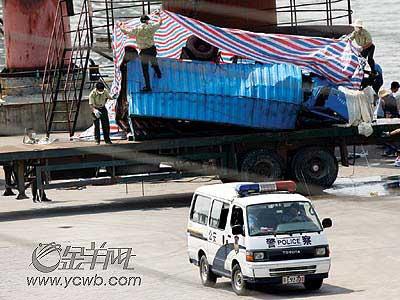 上图:在九江战备码头上,工人对刚打捞起来的车进行封盖。