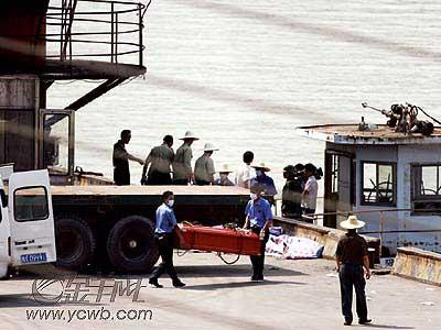 上图:工人将尸体装入殓箱后送上殡仪车运走。