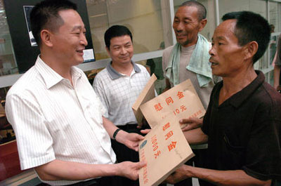 6月22日,王文田(右一)、谢凤运(右二)把慰问金交到河南省周口市驻广州办事处工作人员手中,并委托他将钱捐赠给河南老家的小学。但两位老人表示,救人是很正常的事,他们不能收钱,最后把慰问金捐给了河南老家的两所小学。新华社记者 壮锦 摄