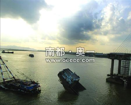 撞断九江大桥的运沙船依旧一头翘起露在江面上,而部分遇难者的遗体仍未打捞出水。