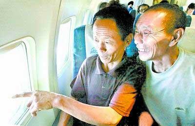 第一次乘坐飞机的两位英雄愉快地欣赏舷窗外美丽的风景。