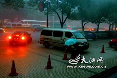 14时30分左右,记者看到南昌上空突然乌云密布,电闪雷鸣,大雨倾盆而下,一时间南昌城如同黑夜一般,路上汽车纷纷亮灯前行。(大江网记者姚海南摄)