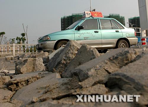 6月25日,一辆出租车在被晒爆的道路上小心行驶。