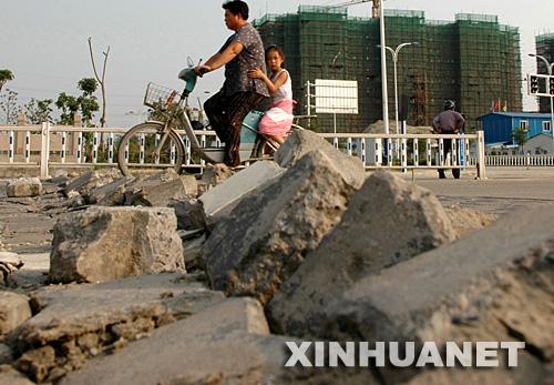 6月25日,市民在被晒爆的道路上小心骑车。