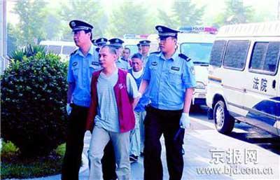 图为:今晨,梁瑞南等4人被押进法庭受审。