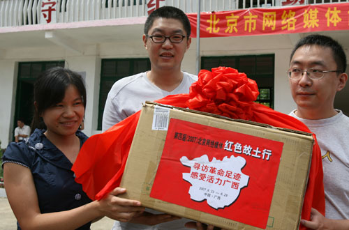 龙和小学教师(左)接受捐赠