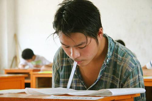 2007年6月26日上午,无臂少年代军颂用牙咬着笔填写中考试卷。