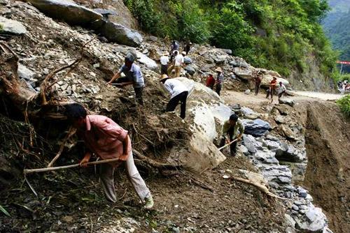 """2007年6月26日,湖北五峰,农民在抢修""""6、22""""特大暴雨水毁公路。"""