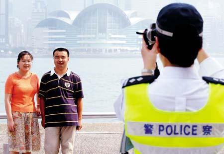 """喊来警察帮忙按下快门,""""自由行""""为香港带来人潮和财源。"""